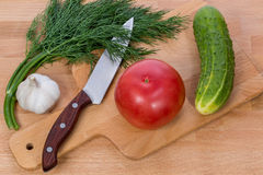 The big pink tomato cucumber dill and knife. Close-up. The big pink tomato cucumber dill and knife lying on a cutting board Royalty Free Stock Photo