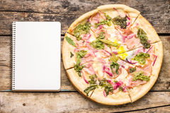 Big pizza with notebook on wooden table. Royalty Free Stock Image