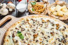 Big pizza with wild mushrooms and cheese on a round cutting boar royalty free stock image
