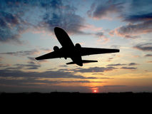 Big plane over sunset. Silhouette of airplane over sunset Stock Photo