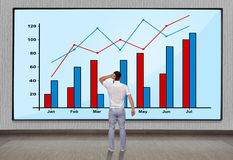 Big plasma with chart. Men looking at big plasma panel with chart on wall Royalty Free Stock Image