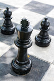Big plastic chess game on checkerboard Royalty Free Stock Photo