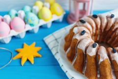 Big plate with cake and hand painted colorful eggs, on towel on blue background. Close up. Decoration for Easter, stock image