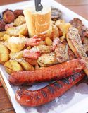 Big plate with delicious variety of meat - grilled steak, meatballs, chicken, sausages, bread and potato fries. At a greek restaurant stock photos
