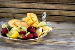 Big plate of fresh fruit on wooden background,. A big plate of fresh fruit on wooden background, there is a place for inscription Royalty Free Stock Images