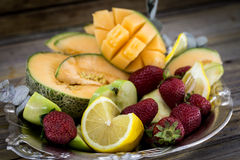 Big plate of fresh fruit on wooden background,. A big plate of fresh fruit on wooden background, there is a place for inscription Stock Images