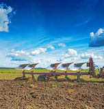 Big plough in work on field at spring agricultural Royalty Free Stock Images