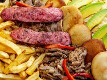 Big portion of pork meat, grilled sausages, potatoes and arepas with avocados