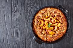 Big portion of a simple and healthy Peach Cobbler. Simple and healthy peach cobbler baked in a black baking dish, on a black wooden table, top view, flat lay stock image