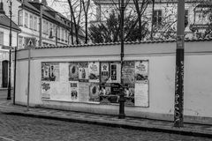 Big poster board with peeling off posters in Prague. Huge poster board full of posters in Prague, stone paved road, corner of the street and a street sign also Royalty Free Stock Image