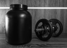 Big pot of food supplement next to a barbell Stock Image