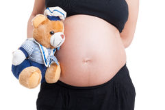 Big pregnant woman belly and plush teddy bear Royalty Free Stock Image