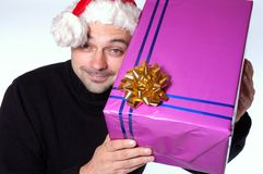 Big present. Man with santa hat holds a big present Royalty Free Stock Images