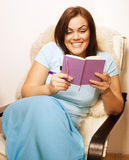 Big pretty young woman at home resting, reading book Stock Photos