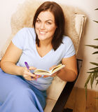 Big pretty young woman at home resting, reading book Royalty Free Stock Images