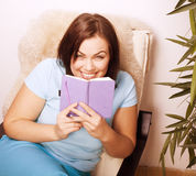 Big pretty young woman at home resting, reading book Royalty Free Stock Photo