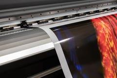 Big professional printer, processing massive vinyl red rolls. royalty free stock photography
