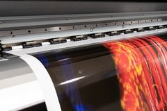 Big professional printer, processing massive vinyl red rolls. stock image