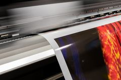 Big professional printer, processing massive vinyl red rolls. stock images