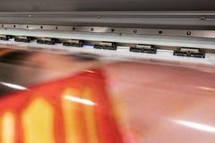 Big professional printer, processing massive vinyl red rolls. stock images