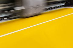 Big professional printer, processing a large scale glossy sheet of yellow paper rolls for color sampling. Moving print head in motion with blur royalty free stock images