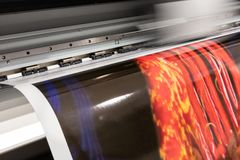 Big professional printer, processing massive vinyl red rolls. stock photography
