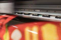 Big professional printer, processing massive vinyl red rolls. stock photo