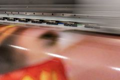 Big professional printer, processing massive vinyl red rolls. Big professional printer, detailed shot of the massive head passing by with motion blur and red stock images