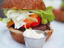 Big proper homemade beef burger. With vegetables and mayonnaise royalty free stock image