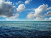 Cloudscape Meets The Blue Ocean Water. Big puffy clouds in the blue sky meets the ocean waters horizon Stock Photos