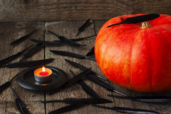 Big pumpkin,  black feathers and  candle Royalty Free Stock Photo