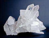 Big quartz crystals. Large crystals of white quartz on dark blue background Stock Photos