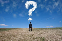 The big question. Businessman standing alone at the field with a lot of questions in his mind Stock Photography