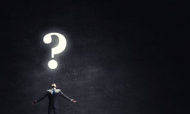 Big question. Businessman with hands spread apart looking above at big question Stock Image