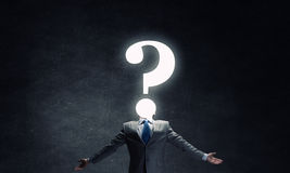 Big question. Businessman with hands spread apart looking above at big question Royalty Free Stock Images