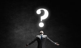 Big question. Businessman with hands spread apart looking above at big question Stock Photography