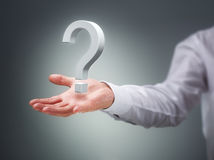The big question. Businessman holding a virtual question mark concept for confusion, choice, searching or decisions Royalty Free Stock Image