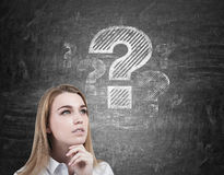 Big question mark and girl's head close up. Close up of a thinking blond woman's head. She is standing near a blackboard with a large question mark drawn Royalty Free Stock Photo