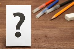 Big question mark on white paper, and stationery as the background. 