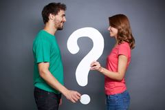 Big question. Portrait of young couple holding paper question mark and looking at on another royalty free stock photo