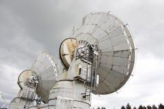 Big radio telescope on cloudy sky background Stock Photo