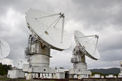 Big radio telescope on cloudy sky background Stock Photo