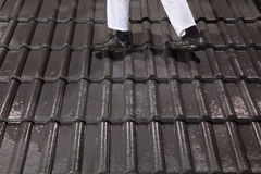Worker walking on roof tiles Stock Photo