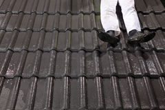 Worker on roof fixing roof tiles Stock Images
