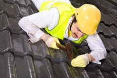 Worker on roof fixing roof tiles Royalty Free Stock Photography