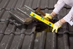 Worker on roof fixing roof tiles Royalty Free Stock Photos