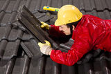 Worker on roof fixing roof tiles Stock Image