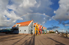 Big rainbow over colorful buildings in Zoutkamp Royalty Free Stock Images