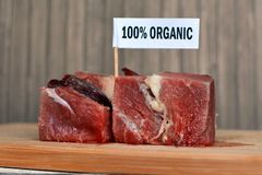Raw red meat chunks on wooden plate with label saying `100 percent organic`, concept for healthy organic food production