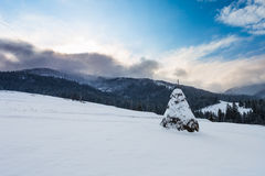 Big reap on hill at winter on mountain background. The big reap on hill at winter on mountain background Stock Photography